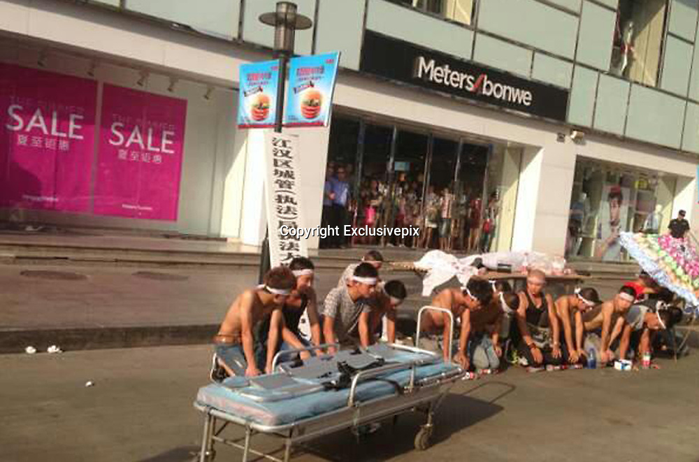 """WUHAN, CHINA - (CHINA OUT) <br /> <br /> Extreme Heat Brings 'Dead' Man Back To Life<br /> <br /> People carry a sheet-covered vendor's """"corpse"""" on a gurney to help him fake his own death for financial gains on August 3, 2013 in Wuhan, Hubei province of China. They claimed that urban management workers had beaten the man to death and demanded tens of thousands of yuan in compensation. The scheme ended up backfiring on the vendor himself because he couldn't bear the heat. ©Exclusivepix"""