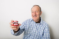 Portrait of smiling senior man holding teeth model against gray background