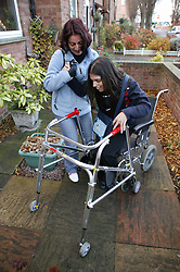Single parent helping daughter out of a wheelchair and into a walking frame,