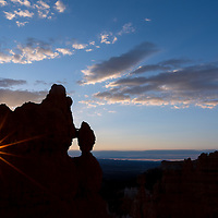 A sunstar at sunrise appears thru one eye of The Mask, a rock structure in Bryce Canyon National Park, Utah