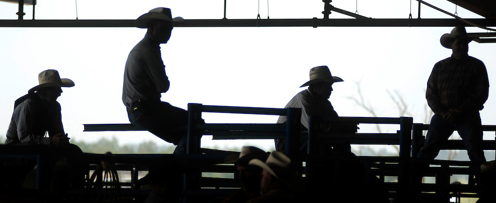 A group of cowboys are silhouetted against the grey sky during a preview show of the Great Southland Stampede Rodeo at the University of Georgia Livestock Instructional Arena on Thursday, April 15, 2010 in Athens, Ga..