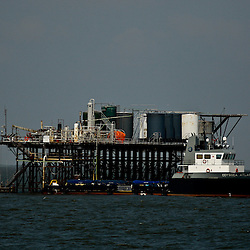 A vessel docks at a tank battery in the Gulf of Mexico off the coast of Louisiana, U.S., on Thursday, July 15, 2010. Photographer: Derick E. Hingle/Bloomberg