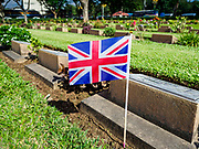 "11 NOVEMBER 2018 - KANCHANABURI, KANCHANABURI, THAILAND: A British flag on a headstone during the Rememberance Day ceremony at the Kanchanaburi War Cemetery in Kanchanaburi, Thailand. Kanchanaburi is the location of the infamous ""Bridge On the River Kwai"" and was known for the ""Death Railway"" built by Japan during World War II using allied, principally British, Australian and Dutch, prisoners of war as slave labor. There are 6,982 people buried in the cemetery, including 5,000 Commonwealth soldiers and 1,800 Dutch soldiers. November 11, 2018 marked the 100th anniversary of the end of World War I, celebrated as Rememberance Day in the UK and the Commonwealth and Veterans' Day in the US.    PHOTO BY JACK KURTZ"