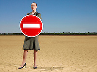 Businesswoman holding 'no entry' sign in desert full length