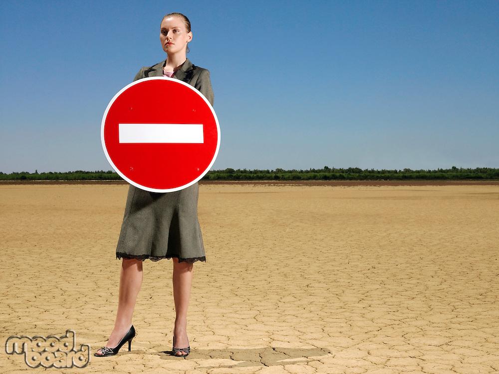 Businesswoman holding 'no entry' sign in desert full length