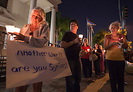 People attend a candlelight vigil as they protest against a US military intervention in Syria on Monday, September 9, 2013 in Los Angeles, California. (Photo by Ringo Chiu/PHOTOFORMULA.com)