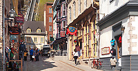 Colorful signs of shops and restaurants on a historic street Rue Sous Le Fort in old Quebec City with funicular in the background. Souvenirs du Lys, Sous le Fort, La Chasse-Galerie boutique, Mouche à feu and other shops and restaurants. Quebec, Canada. Rue Sous-Le-Fort, Ville de Québec.