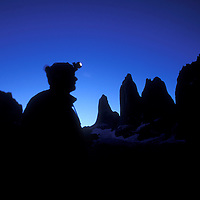Chile, Torres del Paine National Park, Hiker silhouetted at twilight under Torres del Paine rock spires in Patagonia