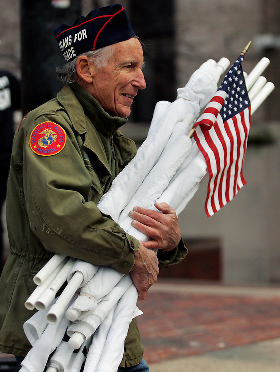 Korean War tank division veteran Dudley Hartung of Somerville, MA carries folded up pro-peace banners following the official Veterans for Peace rally at Government Center on Veterans Day, Wednesday, November 11.  ..Veterans for Peace was not allowed to participate in the official American Legion Veterans Day parade, but instead marched 100 yards behind from the Common to Government Center.  Two years ago, 18 members of Veterans for Peace were arrested while attending an official Veterans Day event at Government Center. ..(Photo by Brooks Canaday)
