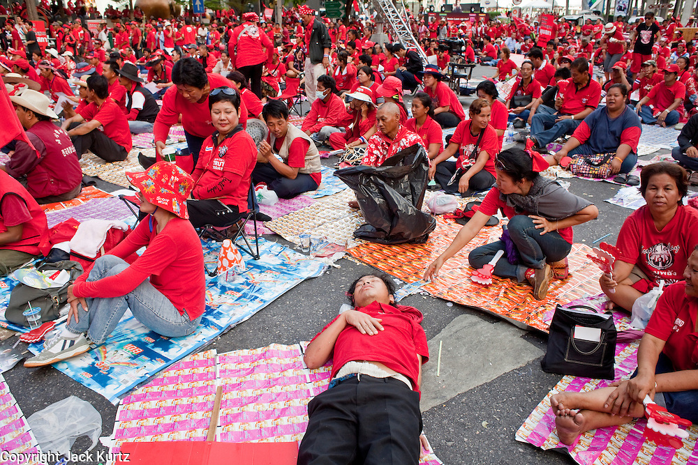 """Apr 4, 2010 - BANGKOK, THAILAND: A Red Shirt protestor tries to sleep surrounded by thousands of his fellow Red Shirts in Bangkok, Apr. 4. Thousands of members of the United Front of Democracy Against Dictatorship (UDD), also known as the """"Red Shirts"""" and their supporters moved their anti government protests into central Bangkok Apr. 4 when they occupied Ratchaprasong intersection, the site of Bangkok's fanciest shopping malls and several 5 star hotels. The Red Shirts are demanding the resignation of current Thai Prime Minister Abhisit Vejjajiva and his government. The protest is a continuation of protests the Red Shirts have been holding across Thailand. They support former Prime Minister Thaksin Shinawatra, who was deposed in a coup in 2006 and went into exile rather than go to prison after being convicted on corruption charges. Thaksin is still enormously popular in rural Thailand. This move, away from their traditional protest site in the old part of Bangkok, has gridlocked the center of the city and closed hundreds of stores and restaurants and several religious shrines. There has not been any violence, but the government had demanded that the Red Shirts return to the old part of the city.   PHOTO BY JACK KURTZ"""