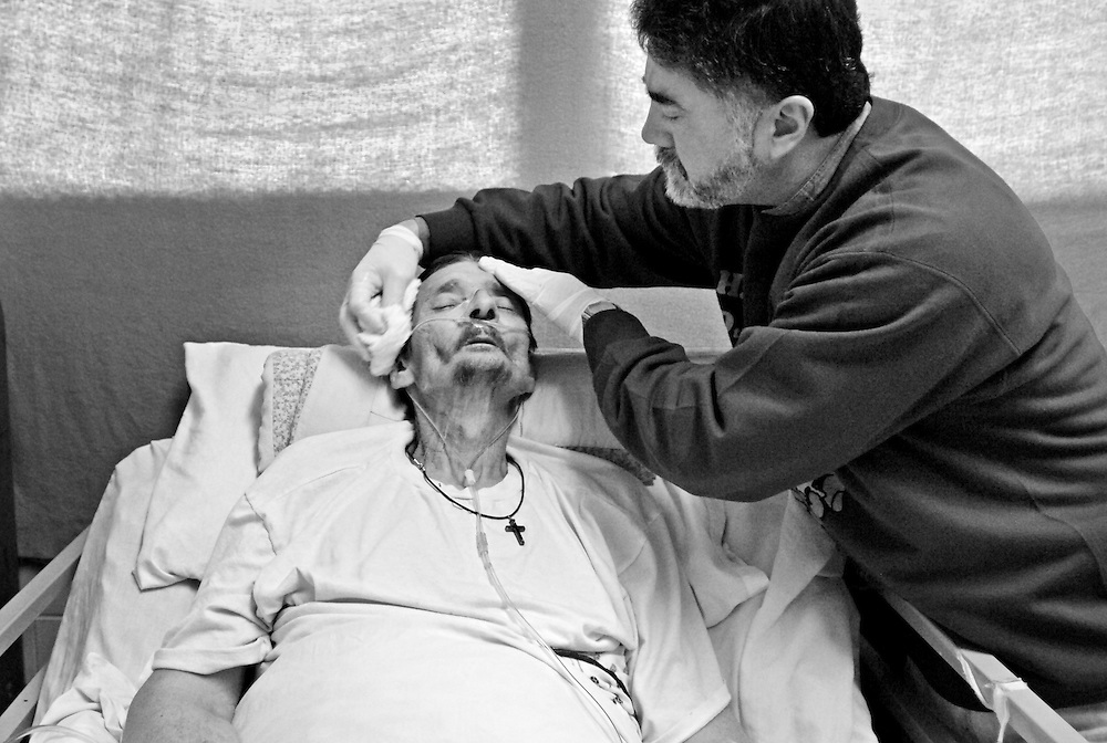 Hospice volunteer Diego Zapata washes  Richard Liggett's face. Liggett, 55, is fighting advanced liver and lung cancers.
