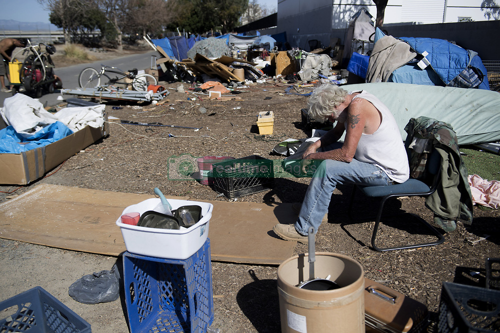January 29, 2018 - Anaheim, California, USA - David Austin takes a break from clearing his belongings along the Santa Ana River Trail in Anaheim on Monday, Jan. 29, 2018. He expected to get housing through a program for military veterans. ''I'll take my duffle bag with clothes, and that's it,'' he said. (Credit Image: © Paul Bersebach/The Orange County Register via ZUMA Wire)