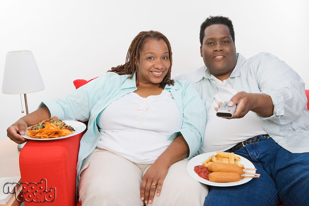 Mid-adult overweight couple sitting on sofa with meal and watching television