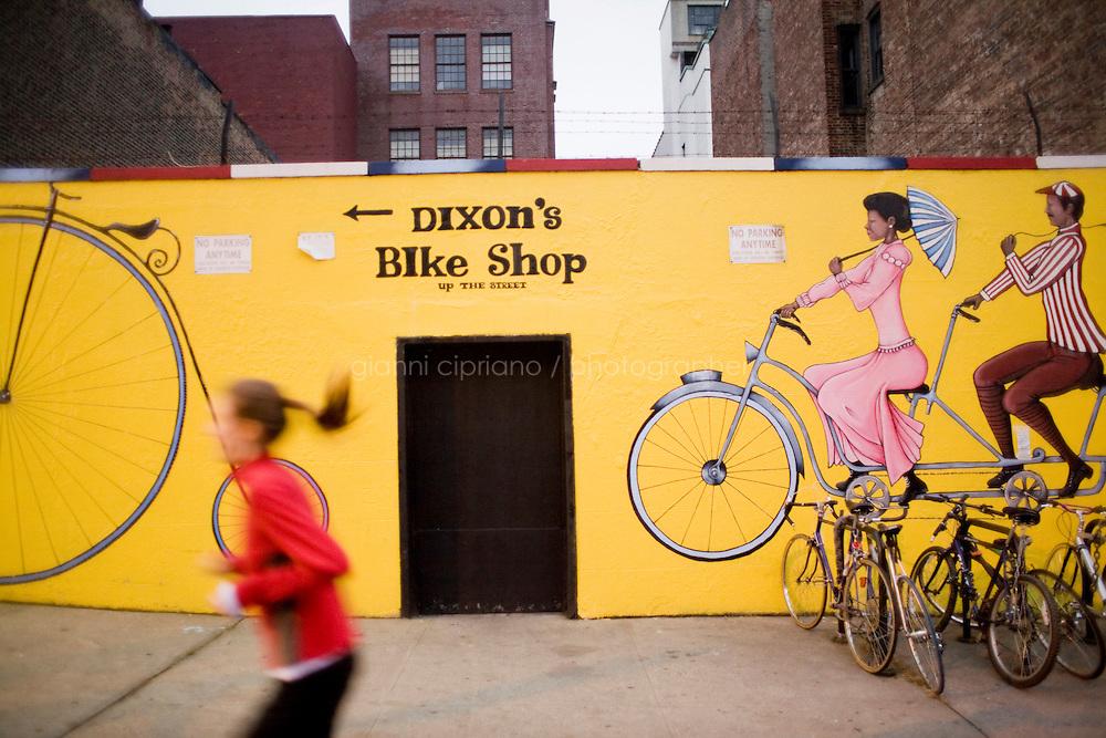 """7 Novembre, 2008. Brooklyn, New York.<br /> <br /> Una ragazza fa jogging passando di fronte ad un'insegna pubblicatario del Dixon's Bike Shop, un negozio di bicicle nella Union Street a Park Slope, Brooklyn, NY, una della vie più famose del quartiere. Park Slope, spesso definito dai newyorkesi come """"The Slope"""", è un quartiere nella zona ovest di Brooklyn, New York, e confinante con Prospect Park.  Park Slope è un quartiere benestante che ha il maggior numero di nascite, la qualità della vita più alta e principalmente abitato da una classe media di razza bianca. Per questi motivi molte giovani coppie e famiglie decidono di trasferirsi dalle altre municipalità di New York a Park Slope. Dal punto di vista architettonico, il quartiere è caratterizzato dai brownstones, un tipo di costruzione molto frequente a New York, e da Prospect Park.<br /> <br /> ©2008 Gianni Cipriano for The New York Times<br /> cell. +1 646 465 2168 (USA)<br /> cell. +1 328 567 7923 (Italy)<br /> gianni@giannicipriano.com<br /> www.giannicipriano.com"""