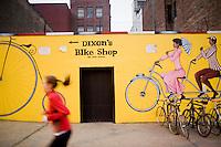 7 Novembre, 2008. Brooklyn, New York.<br /> <br /> Una ragazza fa jogging passando di fronte ad un'insegna pubblicatario del Dixon's Bike Shop, un negozio di bicicle nella Union Street a Park Slope, Brooklyn, NY, una della vie pi&ugrave; famose del quartiere. Park Slope, spesso definito dai newyorkesi come &quot;The Slope&quot;, &egrave; un quartiere nella zona ovest di Brooklyn, New York, e confinante con Prospect Park.  Park Slope &egrave; un quartiere benestante che ha il maggior numero di nascite, la qualit&agrave; della vita pi&ugrave; alta e principalmente abitato da una classe media di razza bianca. Per questi motivi molte giovani coppie e famiglie decidono di trasferirsi dalle altre municipalit&agrave; di New York a Park Slope. Dal punto di vista architettonico, il quartiere &egrave; caratterizzato dai brownstones, un tipo di costruzione molto frequente a New York, e da Prospect Park.<br /> <br /> &copy;2008 Gianni Cipriano for The New York Times<br /> cell. +1 646 465 2168 (USA)<br /> cell. +1 328 567 7923 (Italy)<br /> gianni@giannicipriano.com<br /> www.giannicipriano.com