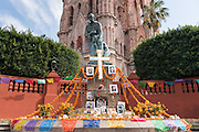 An altar known as an ofrenda around the statue of Statue of Fray Juan de San Miguel decorated for Day of the Dead festival at the Jardin Principal in San Miguel de Allende, Guanajuato, Mexico. The week-long celebration is a time when Mexicans welcome the dead back to earth for a visit and celebrate life.