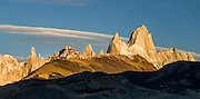 "A golden sunrise spotlights Mount Fitz Roy (3405 meters or 11,170 feet), which rises abruptly on the border between Argentina and Chile in the Southern Patagonian Ice Field in the Andes mountains, near El Chaltén village, in Los Glaciares National Park, Argentina, South America. In 1877, explorer Perito Moreno named ""Cerro Fitz Roy"" for Robert FitzRoy (no space before the capital R) who, as captain of the HMS Beagle, had travelled up the Santa Cruz River in 1834 and charted much of the Patagonian coast. First climbed in 1952 by French alpinists Lionel Terray and Guido Magnone, Mount Fitz Roy has very fickle weather and is one of the world's most challenging technical ascents. It is also called Cerro Chaltén, Cerro Fitz Roy, and Monte Fitz Roy (all with a space before the R). Chaltén comes from a Tehuelche (Aonikenk) word meaning ""smoking mountain"" (explained by frequent orographic clouds). Cerro is a Spanish word meaning hill. El Chaltén village was built in 1985 by Argentina to help secure the disputed border with Chile, and now tourism supports it, 220 km north of the larger town of El Calafate. The foot of South America is known as Patagonia, a name derived from coastal giants, Patagão or Patagoni, who were reported by Magellan's 1520s voyage circumnavigating the world and were actually Tehuelche native people who averaged 25 cm (or 10 inches) taller than the Spaniards. Mount Fitz Roy is the basis for the Patagonia company's clothing logo, after Yvon Chouinard's ascent and subsequent film in 1968.  Panorama stitched from 3 overlapping photos. Published in ""Light Travel: Photography on the Go"" by Tom Dempsey 2009, 2010."