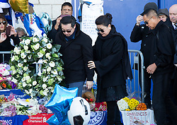 © Licensed to London News Pictures. 29/10/2018. Leicester, UK. Vichai Srivaddhanaprabha's son Aiyawatt and his mother Aimon, look at tributes left outside the King Power Stadium, home of Leicester City FC following the fatal events on Saturday evening. Vichai Srivaddhanaprabha was killed along with two members of his staff, the pilot and a passenger when the helicopter crashed after a Premier League game. Photo credit: Dave Warren/LNP