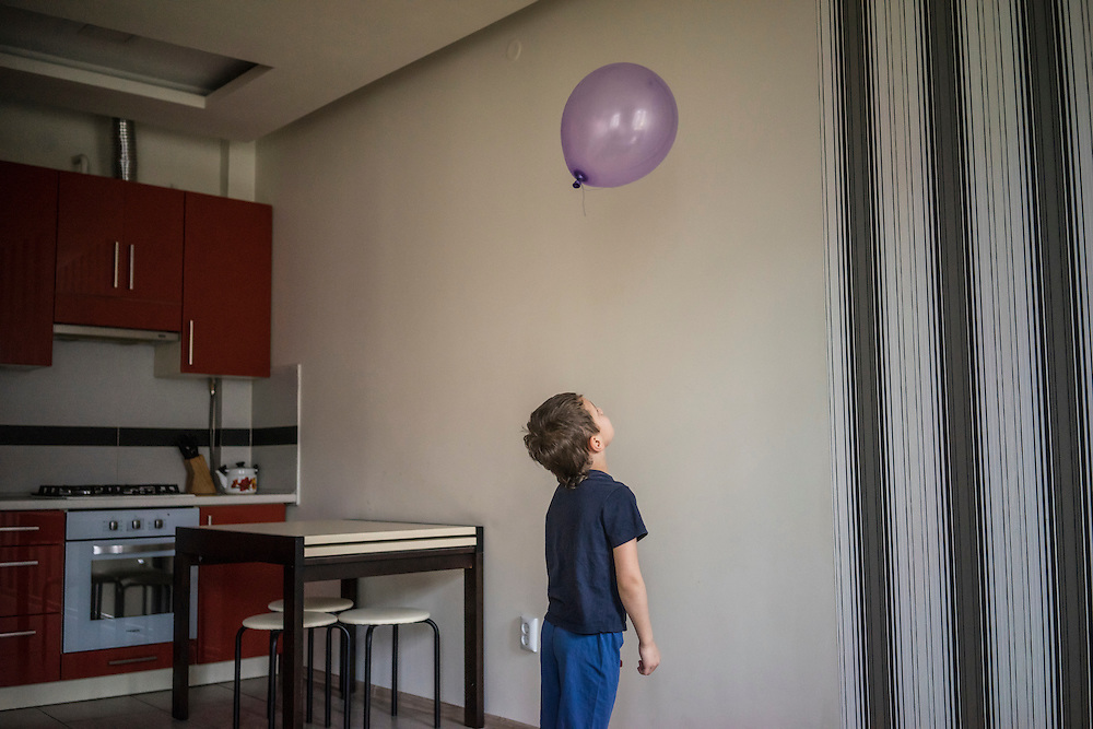 Yaroslav Kirichuk, 6, plays with a balloon on Tuesday, April 28, 2015 in Lviv, Ukraine. After his father joined forces with pro-Russian rebels in eastern Ukraine, his mother Olga left him and other members of her family with anti-Ukrainian views and took her son to Lviv, where they live with a friend. CREDIT: Brendan Hoffman/Prime for the Wall Street Journal UKRMIGRATION