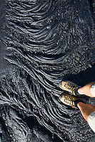 A man's feet and legs standing on Pahoehoe lava in Hawai'i Volcanoes National Park