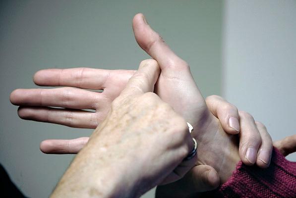 Nederland, Nijmegen, 28-10-2010Een doof-blinde vrouw woont thuis bij haar moeder en beschikt over moderne hulpmiddelen, zoals een computer, een leesloupe en een trilwekker in bed. Gebarentaal, letter G.Foto: Flip Franssen
