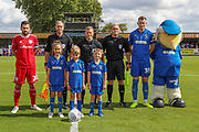 AFC Wimbledon striker Joe Pigott (39), Accrington Stanley defender Seamus Conneely (28) and Mascot prior to kick off during the EFL Sky Bet League 1 match between AFC Wimbledon and Accrington Stanley at the Cherry Red Records Stadium, Kingston, England on 17 August 2019.
