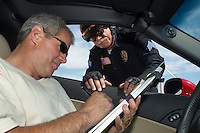 Police officer watching driver signing papers, view from car