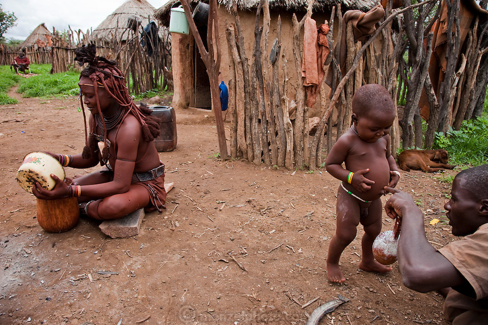 Viahondjera Musutua's older brother plays with her son as she eats porridge left over from breakfast in Opuwo, northwestern Namibia. (From the book What I Eat: Around the World in 80 Diets.) MODEL RELEASED.
