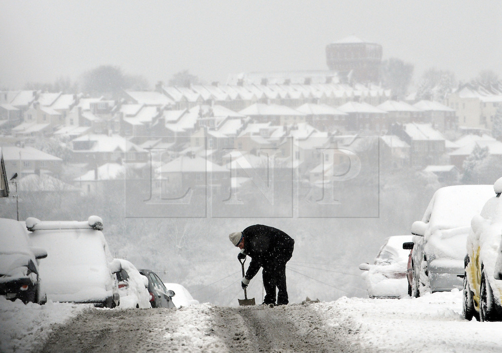 © Licensed to London News Pictures. 18/01/2013. Bristol, UK. A man clears the road of heavy snow in Hazelbury Road in Bristol. 18 January 2013..Photo credit : Simon Chapman/LNP