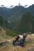 Guide and travelers looking at map overlooking Machu Picchu  Peru  Not Released