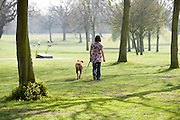 A woman takes a walk alone in a park with her dog on a lead.