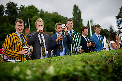 © Licensed to London News Pictures. 28/06/2017. London, UK. Spectators in rowing club colours watch day one of the Henley Royal Regatta, set on the River Thames by the town of Henley-on-Thames in England.  Established in 1839, the five day international rowing event, raced over a course of 2,112 meters (1 mile 550 yards), is considered an important part of the English social season. Photo credit: Ben Cawthra/LNP