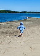 Boy running along the beach, Cape Cod, Massachusetts, USA.