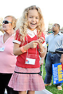 "East Meadow, NY - OCTOBER 15: At Obama Rally, close-up of laughing blond girl about four years old looking at viewer. The happy child is shown from above knees up, standing on chair, and behind her are diverse supporters, one holding ""Obama Biden"" sign, in crowd at Obama Rally at Eisenhower Park October 15, 2008 in East Meadow, New York, less than 2 miles away from Hofstra University, the site of final presidential debate held later that night."