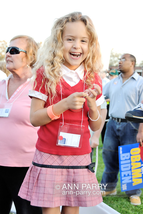 """East Meadow, NY - OCTOBER 15: At Obama Rally, close-up of laughing blond girl about four years old looking at viewer. The happy child is shown from above knees up, standing on chair, and behind her are diverse supporters, one holding """"Obama Biden"""" sign, in crowd at Obama Rally at Eisenhower Park October 15, 2008 in East Meadow, New York, less than 2 miles away from Hofstra University, the site of final presidential debate held later that night."""