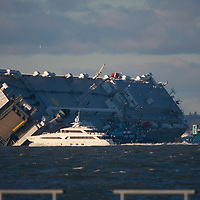 Cowes, Isle of Wight. 6th January, 2015. Life goes on in The Solent. Luxury Motor Cruiser passes close to capsized car carrier Hoegh Osaka in the late afternoon sunshine. Surveyors and survey ships are in attendance to assess the state of the ship and its cargo. Windy weather is expected in the next few days. Two figures can be seen abseiling down the main deck upper middle area. © Patrick Eden