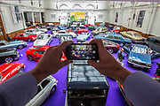 UNITED KINGDOM, London: 24 April 2018 A member of staff takes a picture of a wide selection of classic vintage cars in The Royal Horticultural Halls, Westminster. The car forms part of the Spring Classics: An Important Auction of Fine Historic Automobiles at The Royal Horticultural Halls, Westminster. The auction will see a collection of privately owned cars be auctioned this evening April 24th 2018. Rick Findler  / Story Picture Agency