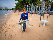 "26 SEPTEMBER 2014 - PATTAYA, CHONBURI, THAILAND: A woman who works for a beach umbrella rental cleans up at the end of the day on Pataya Beach. Pataya, a beach resort about two hours from Bangkok, has wrestled with a reputation of having a high crime rate and being a haven for sex tourism. After the coup in May, the military government cracked down on other Thai beach resorts, notably Phuket and Hua Hin, putting military officers in charge of law enforcement and cleaning up unlicensed businesses that encroached on beaches. Pattaya city officials have launched their own crackdown and clean up in order to prevent a military crackdown. City officials have vowed to remake Pattaya as a ""family friendly"" destination. City police and tourist police now patrol ""Walking Street,"" Pattaya's notorious red light district, and officials are cracking down on unlicensed businesses on the beach.     PHOTO BY JACK KURTZ"