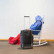A stranded traveler at Charlotte-Douglas International airport sleeps in on the the airports famous white rocking chairs.
