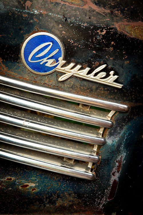 The Chrysler logo on the remains of an old car.