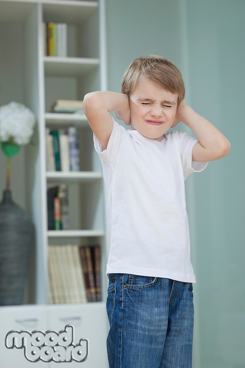 Frustrated boy covering his ears with hands at home