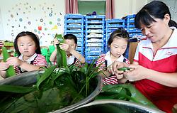 June 15, 2018 - Lianyungan, Lianyungan, China - Lianyungang, CHINA-15th June 2018: Pupils learn to make rice dumplings in Lianyungang, east China's Jiangsu Province, June 15th, 2018, marking the upcoming Dragon Boat Festival. (Credit Image: © SIPA Asia via ZUMA Wire)