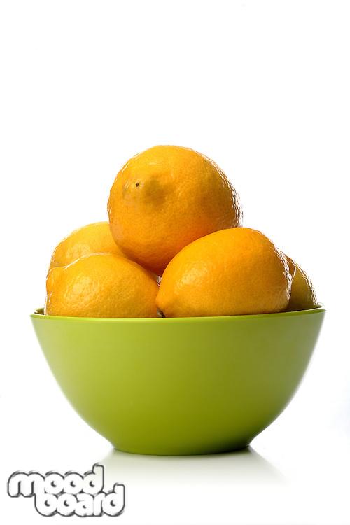 Studio shot of lemons in green bowl