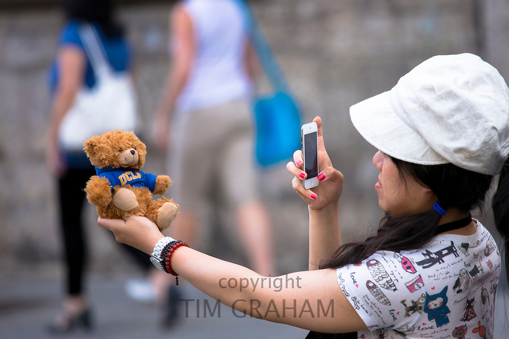 Asian tourist photographs souvenir teddy bear with smartphone in Innsbruck, Austria