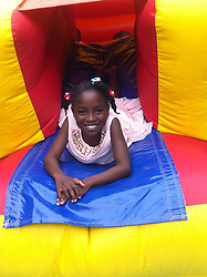 Girl in bouncy castle at children's party, UK