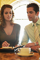 Man and woman sitting in cafe looking at daily organizer.