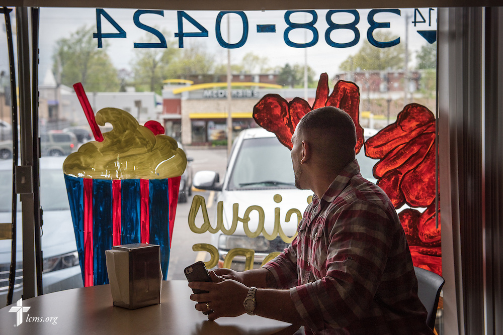 Micah Glenn, a fourth-year Master of Divinity student at Concordia Seminary, St. Louis and new national missionary to Ferguson, looks out the window towards the McDonald's restaurant during lunch on Wednesday, April 20, 2016, in Ferguson, Mo. The McDonald's is known as the focal point of violent clashes between law enforcement and protesters following the shooting death of Michael Brown almost two years ago.  LCMS Communications/Erik M. Lunsford