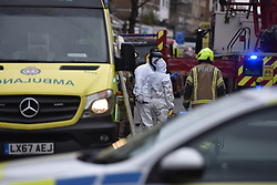 © Licensed to London News Pictures. 01/04/2020. London, UK. Ambulance workers and the fire brigade at an incident involving all emergency services where a suspected COVID-19 case was isolatedand removed from their home. Uxbridge Road in Shepherd's Bush was closed for an hour as ambulance, fire brigade and police attended, extracting the patient by crane from a three story apartment building in West London. PPE (personal protective equipment) was in evidence, with the fire brigade using full facerespirators normally reserved for firefighting. A police officercommented the Metropolitan police force are issued only with rubber gloves. Ambulance workers decontaminated the scene and reusable equipment before moving on.  Photo credit: Guilhem Baker/LNP