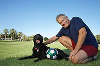 Senior man petting dog beside soccer ball in park