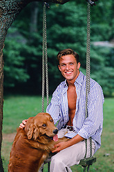 All American man sitting on a rope swing with a dog jumping up on his lap